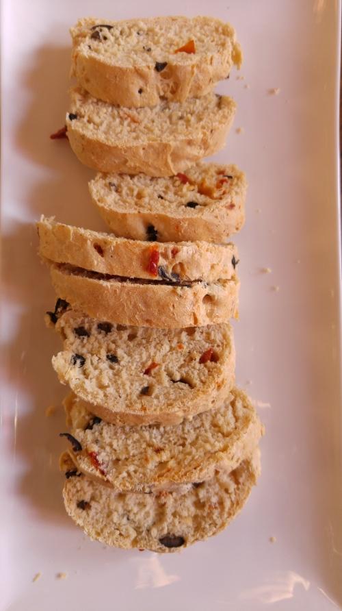 Selbstgebackenes Ciabatte mit Oliven und getrockneten Tomaten, grob nach diesem Rezept.